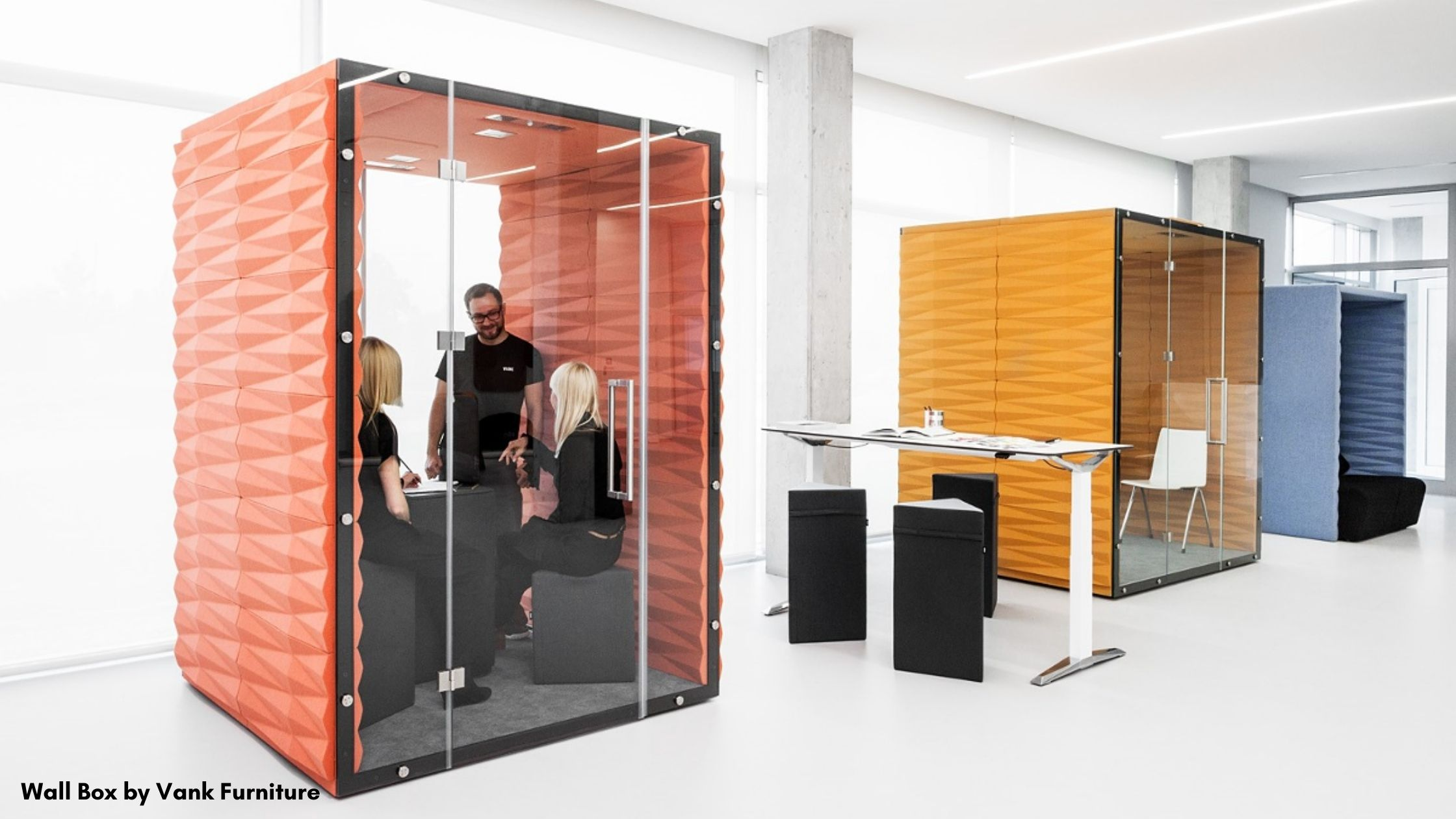 People having a meeting in an an office pad made of orange acoustic panels and glass.