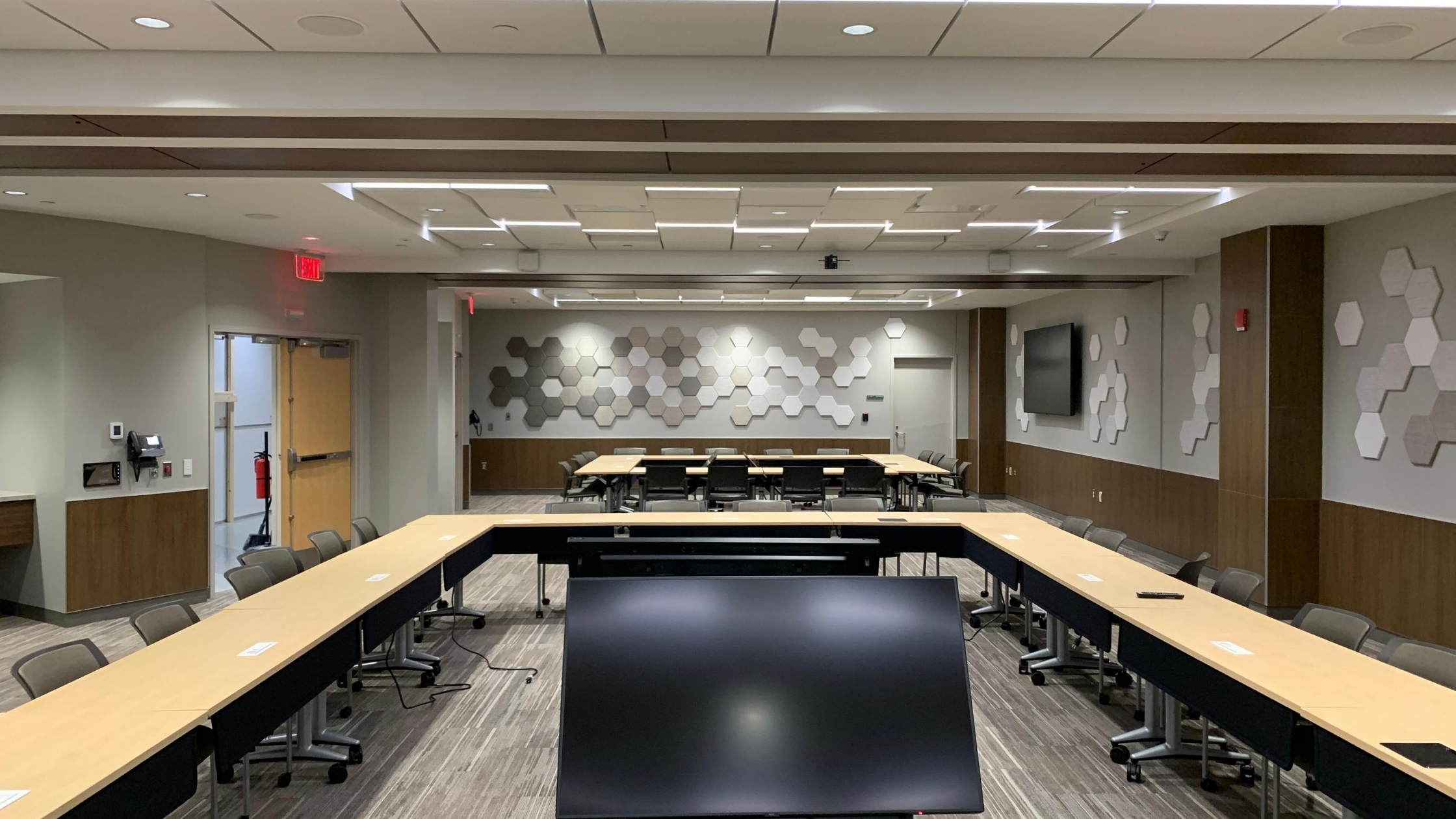 Office meeting room with two Skyfold operable partitions recessed in the ceiling and with hexagonal acoustic tiles on the wall.