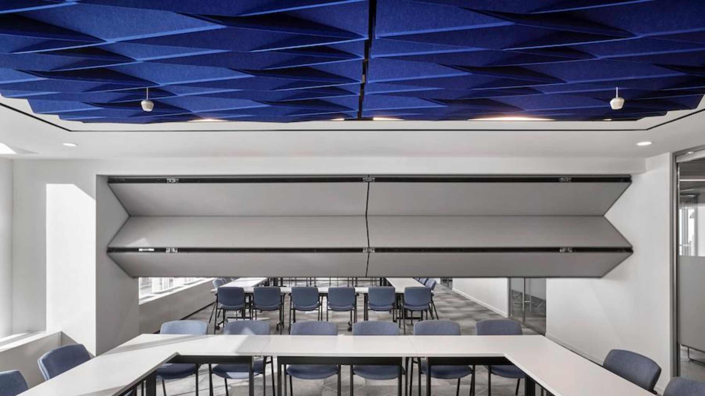 White Skyfold Classic operable partition folding from the ceiling to subdivide an office conference room that has blue acoustic ceiling baffles.